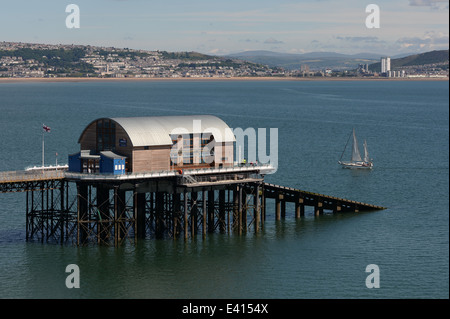 yacht sails passed mumbles lifeboat station on the end of the pier with Swansea city in the background - Stock Photo