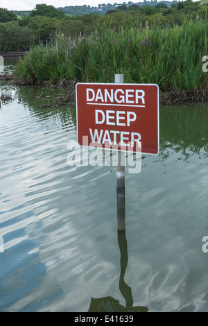 Danger warning sign for deep water. Visual metaphor for concept of financially 'staying afloat' or 'keeping afloat'. - Stock Photo