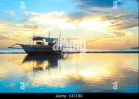 Tropical landscape with traditional Philippines boats at sunset - Stock Photo