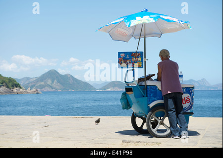 RIO DE JANEIRO, BRAZIL - FEBRUARY 11, 2014: Brazilian beach vendor selling ice cream stands at the entrance to Red - Stock Photo