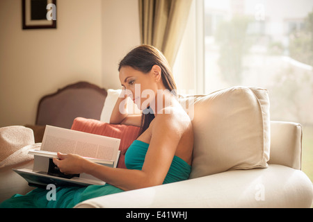 Young woman sitting in armchair reading book - Stock Photo