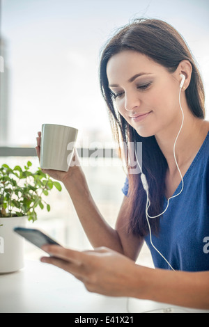 Young woman listening to music on smartphone - Stock Photo