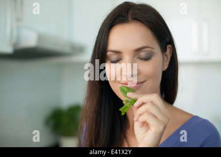 Portrait of young woman smelling basil - Stock Photo