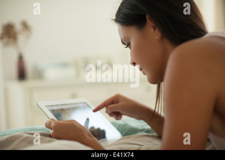 Young woman lying on bed using digital tablet - Stock Photo