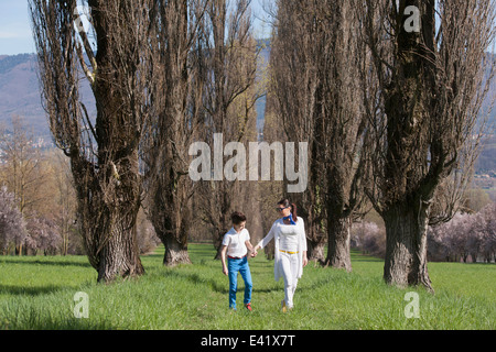 Twelve year old boy and mature mother strolling along tree lined field - Stock Photo