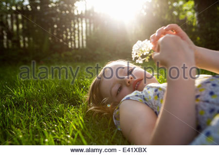 Girl with dandelion clock, lying on back on grass - Stock Photo