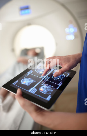Radiographer looking at brain scan image on digital tablet - Stock Photo