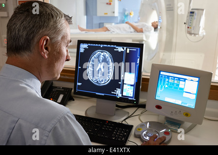 Radiologist looking at brain scan image on computer screen - Stock Photo