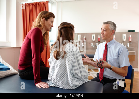 Doctor talking to patient and mother - Stock Photo
