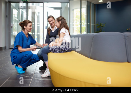 Nurse speaking to girl in hospital waiting room - Stock Photo