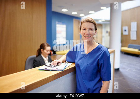 Nurse standing in hospital waiting room - Stock Photo