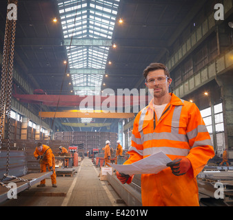 Engineer holding plans in marine fabrication factory, portrait - Stock Photo