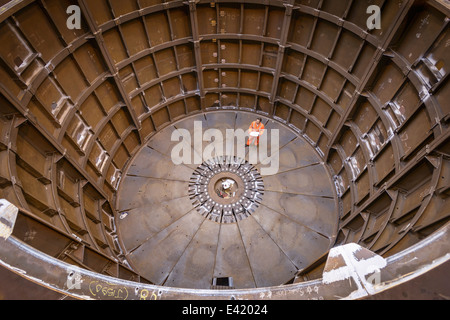 Engineer inspecting marine fabrication used for cable laying, high angle view - Stock Photo