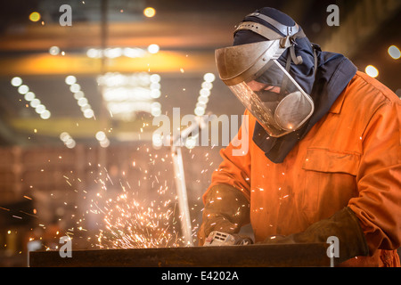Worker grinding metal construction in marine fabrication factory - Stock Photo