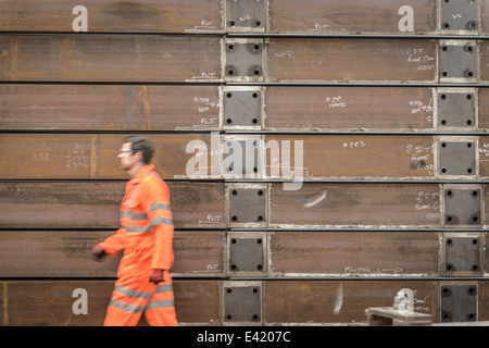 Engineer walking past marine fabrication in factory - Stock Photo