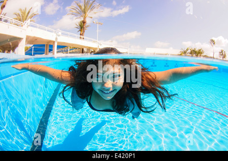 Girl free diving under water in swimming pool - Stock Photo