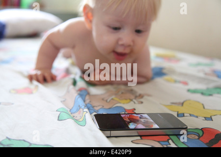 Baby plays with smartphone on bed - Stock Photo