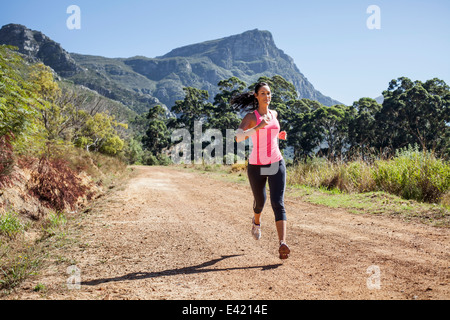 Young woman jogging in forest - Stock Photo