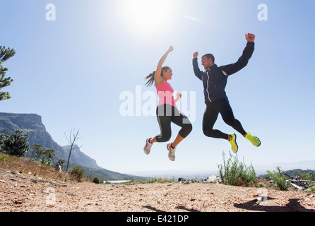 Young joggers jumping in mid air - Stock Photo
