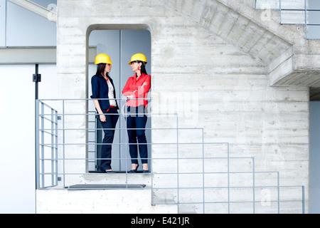 Businesswomen in safety helmet at balcony - Stock Photo