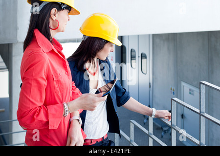 Businesswomen in safety helmet at balcony - Stock Photo