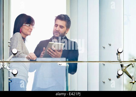 Businessman and woman using digital tablet at balcony - Stock Photo