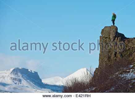 Climber on top of cliff, Baulur, West Iceland - Stock Photo