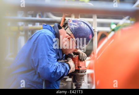 Engineer drilling during power station outage - Stock Photo