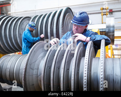 Engineers inspecting turbine during power station outage, portrait - Stock Photo