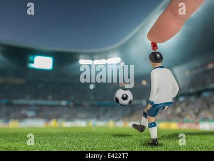 Digitally generated image of soccer player kicking ball in floodlit stadium - Stock Photo