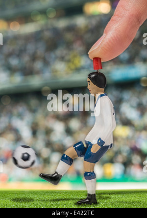 Digitally generated image of soccer player kicking ball in stadium - Stock Photo