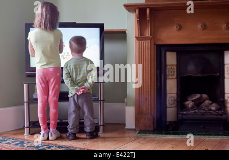 Rear view of sister and brother standing too close to and watching TV - Stock Photo