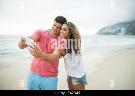 Young couple taking selfie on Ipanema Beach, Rio de Janeiro, Brazil - Stock Photo
