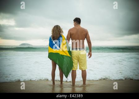 Young couple, woman wrapped in brazilian flag, Ipanema Beach, Rio de Janeiro, Brazil - Stock Photo