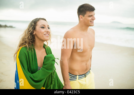 Young couple strolling on beach, woman wrapped in brazilian flag, Ipanema Beach, Rio de Janeiro, Brazil - Stock Photo