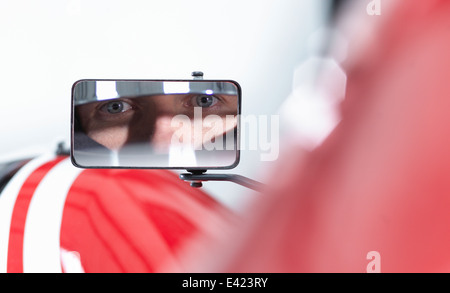 Portrait of racing car driver reflected in wing mirror of supercar - Stock Photo