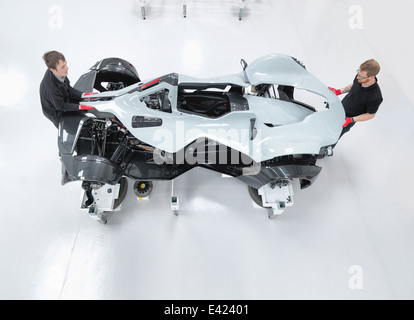 Two engineers assembling supercar in sports car factory, overhead view - Stock Photo