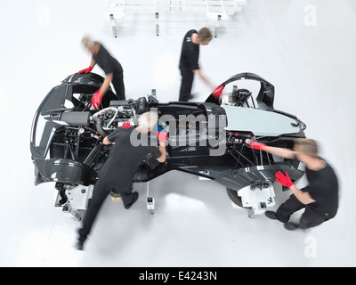 Engineers assembling supercar in sports car factory, overhead view - Stock Photo