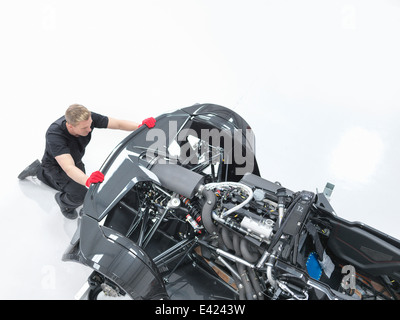Engineer assembling supercar in sports car factory, high angle view - Stock Photo