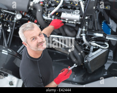 Portrait of engineer assembling supercar in sports car factory, high angle view - Stock Photo