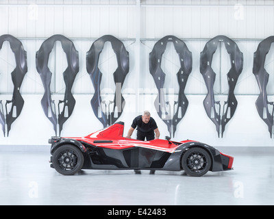 Engineer Inspecting Carbon Fibre Car Body Shell In Sports Car