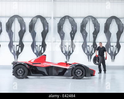 Engineer carrying wheel to supercar in factory with carbon fibre car body shells hanging on wall - Stock Photo