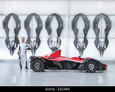 Racing driver with supercar in factory with carbon fibre car body shells hanging on wall - Stock Photo