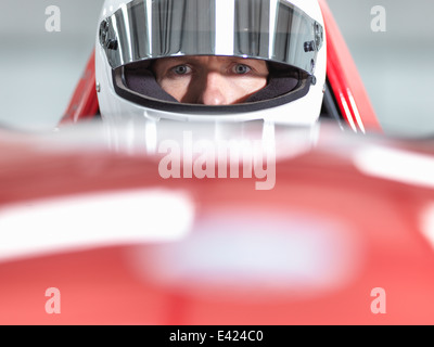 Close up portrait of racing car driver wearing helmet in supercar - Stock Photo