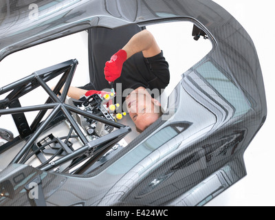 Engineer assembling supercar in sports car factory, overhead view - Stock Photo