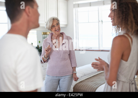 Senior woman guiding couple in holiday apartment - Stock Photo