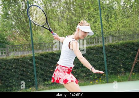 Mature woman playing tennis - Stock Photo