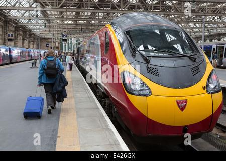 Passengers making their way onto a Virgin train, stopped in Glasgow Central Railway Station, Glasgow, Scotland, - Stock Photo