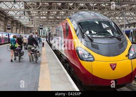 Two cyclists boarding a Virgin train at Glasgow Central railway station, Glasgow, Scotland, UK - Stock Photo