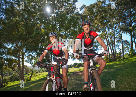 Cyclists riding bicycle in park - Stock Photo